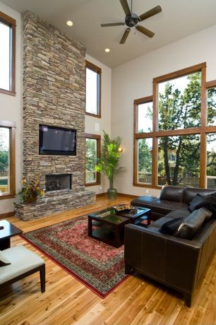 Modern Living Room with Interior stone wall, Leather sectional sofa, stone fireplace, Oriental rug, Ceiling fan