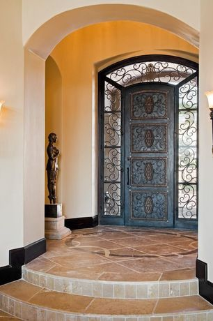 Mediterranean Entryway with limestone floors, Wall sconce, High ceiling, specialty door