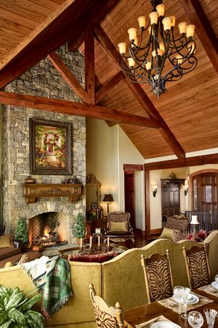 Country Great Room with Wall sconce, Built-in bookshelf, High ceiling, stone fireplace, Chandelier, Exposed beam