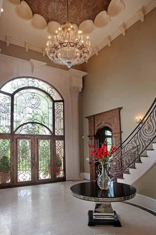 Mediterranean Entryway with French doors, High ceiling, Custom door, Crown molding, can lights, stone tile floors, Chandelier