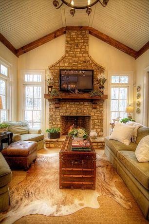 Country Great Room with Exposed beam ceiling, Animal skin rug, Tufted distressed leather ottoman, Stone fireplace surround