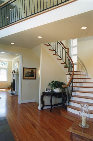 Traditional Staircase with High ceiling, curved staircase, picture window, Hardwood floors