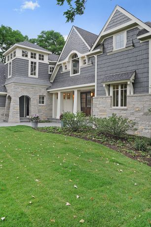 Traditional Exterior of Home with Natural stone exterior wall, Double wide front door, Arch window, Stone columns