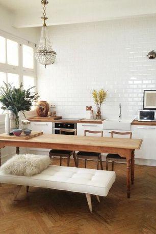 Contemporary Dining Room with interior brick, Hardwood floors, Built-in bookshelf, Chandelier, Exposed beam