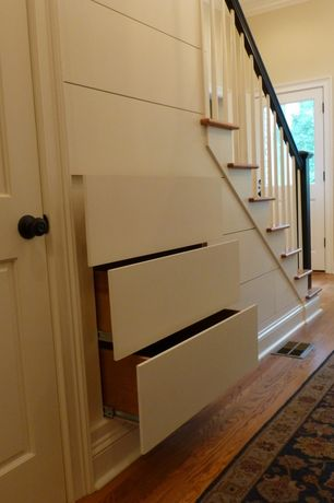 Traditional Entryway with Under Stairs Storage, Built-in bookshelf, Glass panel door, Laminate floors, Under stair storage