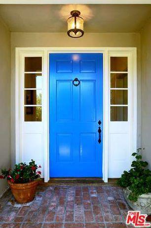 Traditional Front Door with 6-panel exterior door, exterior brick floors
