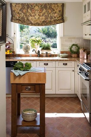 Traditional Kitchen with French vintage copper and brass canister set of 3, European terra cotta tile flooring, Raised panel