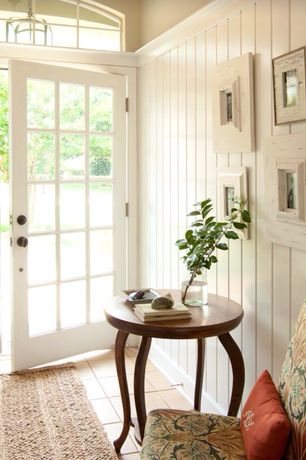 Country Entryway with Floral upholstered parsons chair, Arched window, French doors, limestone tile floors, Wainscotting