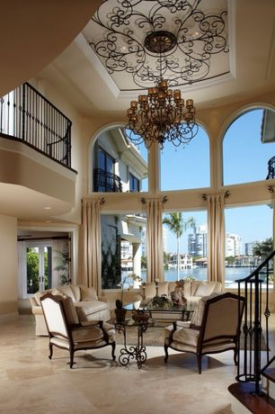 Mediterranean Living Room with sandstone tile floors, Arched window, Balcony, High ceiling, Cement fireplace, Chandelier
