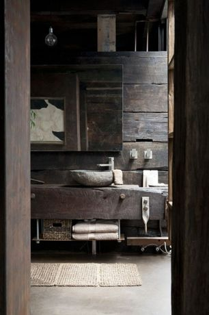 Rustic Master Bathroom with Signature hardware dark grey river stone vessel sink, linen and towel storage cabinet