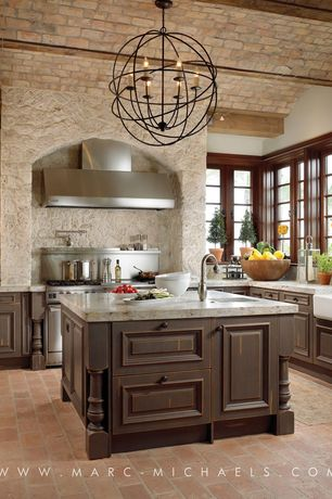 Mediterranean Kitchen with Kitchen island, limestone tile floors, U-shaped, Chandelier, Glass panel, Raised panel, Flush