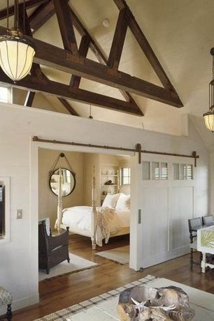 Country Master Bedroom with Hardwood floors, High ceiling, Hallway sliding door in a deep blue, Built-in bookshelf