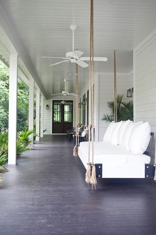 Traditional Porch with Large potted palm, Glass panel door, Suspended outdoor daybed, Modern filament sconce - bronze