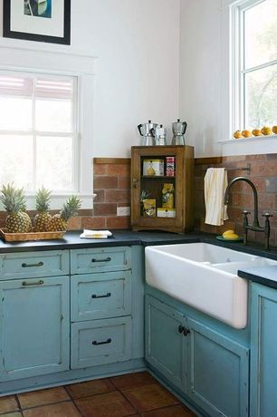 Country Kitchen with Flat panel cabinets, terracotta tile floors, Soapstone counters, Farmhouse sink, Stone Tile, Flush