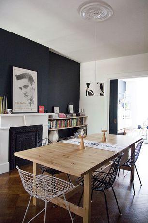 Modern Dining Room with Hardwood floors, Wire mesh dining chairs by woodard, Built-in bookshelf, pocket door, Pendant light
