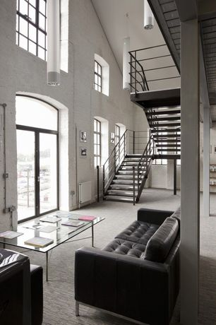 Contemporary Great Room with High ceiling, Transom window, Loft, Columns, Exposed beam, Pendant light, interior brick, Carpet