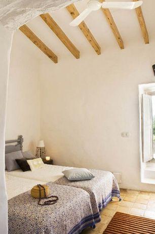 Rustic Guest Bedroom with Ceiling fan, Standard height, specialty door, Wall sconce, Exposed beam, terracotta tile floors