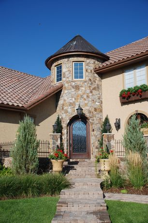 Traditional Front Door with Arched door, Arched doorway, Exterior stone wall, Fence, Turret, Exterior stucco, French doors