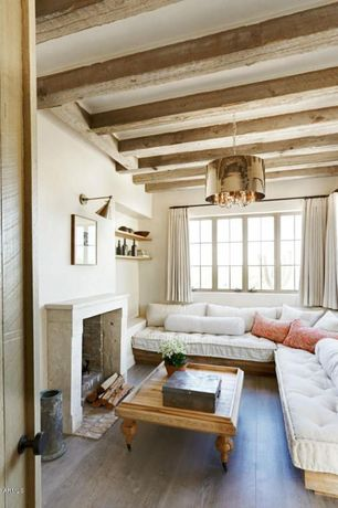 Eclectic Living Room with Built-in bookshelf, Cement fireplace, specialty door, Pendant light, Exposed beam, Window seat