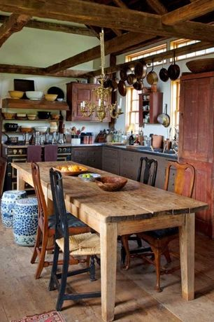 Rustic Dining Room with Reclaimed cabinets, Chandelier, Hardwood floors, Exposed beam, Built-in bookshelf, Farmhouse table