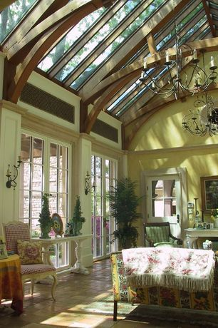 Traditional Living Room with Glass panel door, French doors, Exposed beam, High ceiling, terracotta tile floors, Chandelier