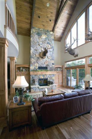Rustic Living Room with Hardwood floors, Balcony, Transom window, Built-in bookshelf, Loft, High ceiling, stone fireplace