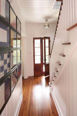 Cottage Entryway with Glass panel door, Built-in bookshelf, flush light, Hardwood floors