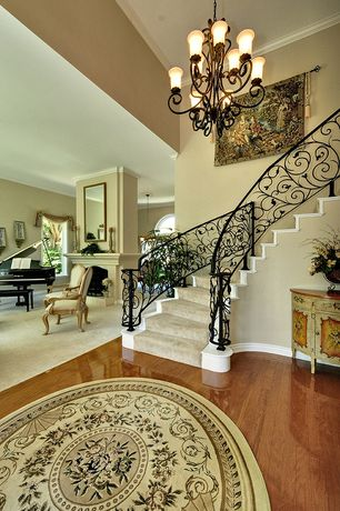 Traditional Staircase with High ceiling, curved staircase, Chandelier, Laminate floors, Crown molding
