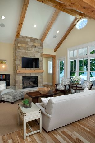 Contemporary Living Room with stone fireplace, Built-in bookshelf, Hardwood floors, High ceiling, Exposed beam, French doors