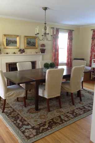 Traditional Dining Room with Hardwood floors, Crown molding, Cement fireplace, Chandelier