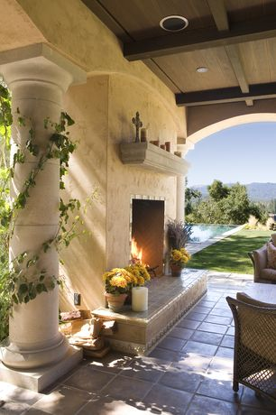 Mediterranean Porch with exterior tile floors, Tuscan order column, Outdoor fireplace, Screened porch