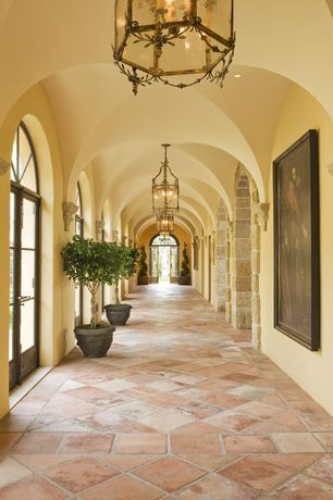 Mediterranean Hallway with Pendant light, Arched window, terracotta tile floors, French doors, can lights, High ceiling