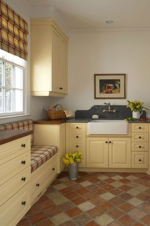 Country Laundry Room with Undermount sink, terracotta tile floors, Window seat, Built-in bookshelf