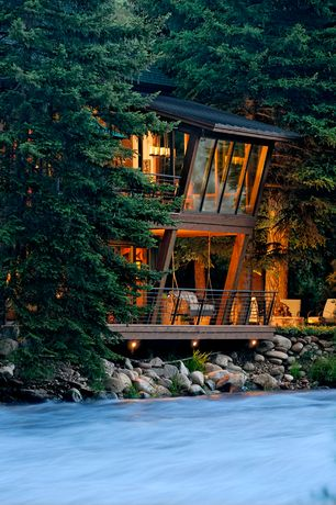 Rustic Exterior of Home with Cantilevered wall, Floor to ceiling windows, Custom slanted windows