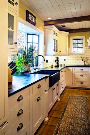 Country Kitchen with Inset cabinets, Wood counters, Kitchen island, European terra cotta tile flooring, Farmhouse sink