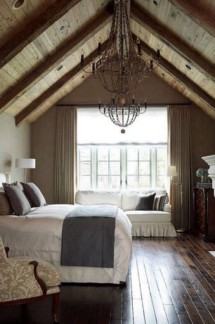 Country Master Bedroom with Andrew martin grasscloth museum wallcovering, Cement fireplace, Exposed beam, Chandelier