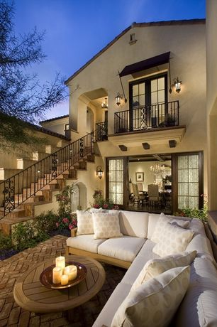Mediterranean Patio with Goldenteak Teak Round Coffee Table, exterior brick floors, Custom Historic Railing, French doors