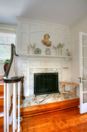 Traditional Hallway with High ceiling, Wainscotting, Crown molding, Glass panel door, Hardwood floors, stone fireplace