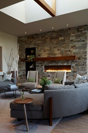 Contemporary Living Room with Exposed beam, Standard height, stone fireplace, picture window, Built-in bookshelf, can lights
