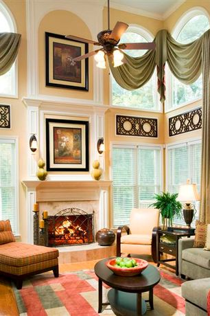 Traditional Living Room with stone fireplace, Wall sconce, Crown molding, Fireplace, Ceiling fan, metal fireplace, Valance