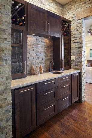 Contemporary Bar with Er cabinets in java colored stain, Hardwood floors, Built-in bookshelf, Dry stacked stone veneer wall