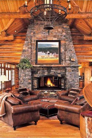 Rustic Living Room with High ceiling, Chandelier, Hardwood floors, stone fireplace, Fireplace, Exposed beam, can lights