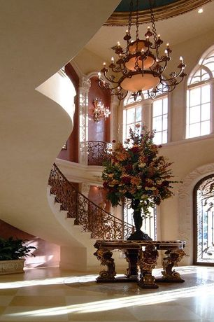 Mediterranean Entryway with travertine tile floors, Arched window, High ceiling, Balcony, Chandelier, Crown molding
