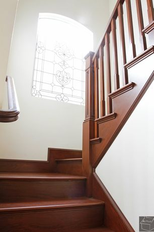 Traditional Staircase with High ceiling, Arched window, Hardwood floors, curved staircase