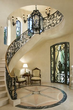 Mediterranean Staircase with Wall sconce, flush light, complex marble floors, French doors, Cathedral ceiling