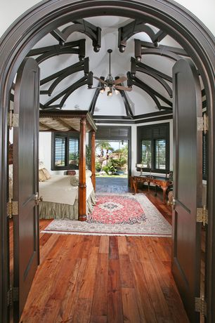 Traditional Master Bedroom with Hardwood floors, Ceiling fan, specialty door, Chandelier, Exposed beam, Crown molding
