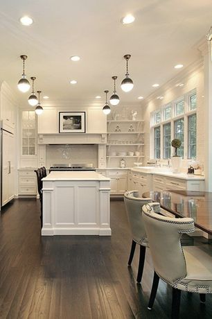 Traditional Kitchen with Corian counters, Breakfast bar, Crown molding, Glass panel, Kitchen island, Flat panel cabinets