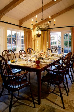 Country Dining Room with slate floors, can lights, French doors, Casement, Wall sconce, Chandelier, Exposed beam