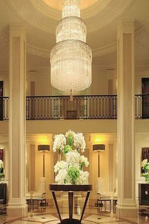 Traditional Entryway with can lights, Paint, Chandelier, Balcony, Columns, High ceiling, simple marble floors, Crown molding