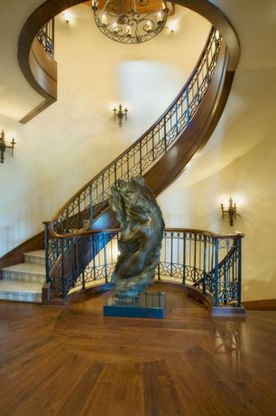 Mediterranean Staircase with Chandelier, Hardwood floors, Wall sconce